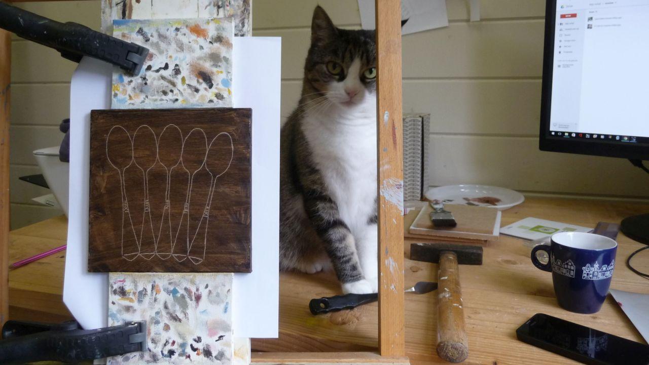 Kat in atelier achter schildersezel
